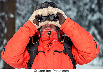 man with binoculars looking at camera, shooting in winter forest