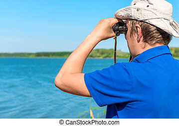 man with binoculars looks for something on the lake