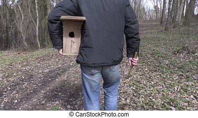 Man with birdhouse and hammer on path in the park