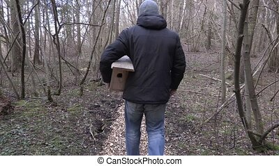 Man with birdhouse and hammer walking on path