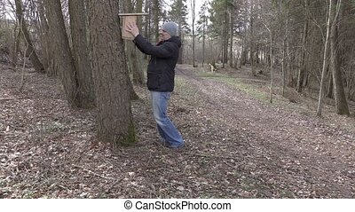 Man with birdhouse near tree in the park