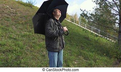 Man with black umbrella during rain