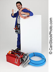 Man with blank board and tools, pointing at cellphone