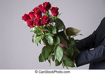 Man with bouquet of red roses on a gray background