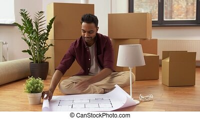 man with boxes and blueprint moving to new home - moving,...