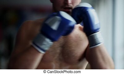 Man with Boxing gloves Boxing in front of the camera close up. Close-up of young man punching. Boxer performing uppercut.