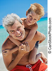 Happy smiling father man and child boy playing at sardinia sea beach