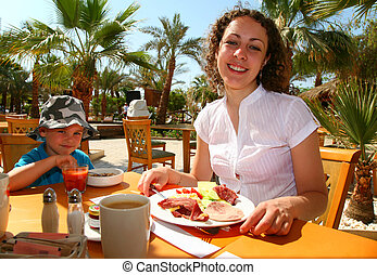 man with boy in tropical cafe