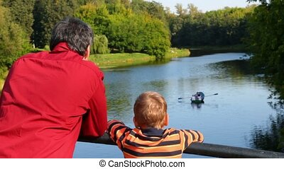man with boy looks at boat