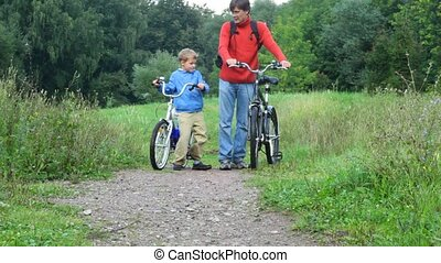 man with boy talking, then riding on bicycles in park