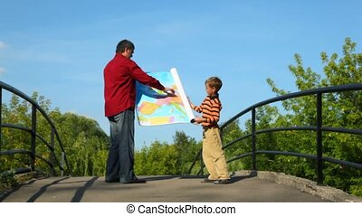 man with boy unrolling map of europe