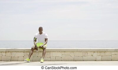 Man with brightly colored shorts and gym shoes seated on...