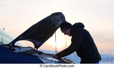 Man with broken car on side of winter road. Sunset time