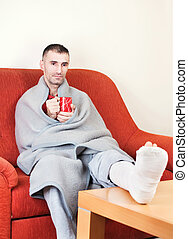 man with broken leg - man with a broken leg on a sofa at...