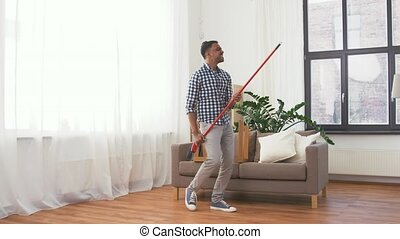 man with broom cleaning and having fun at home - cleaning,...