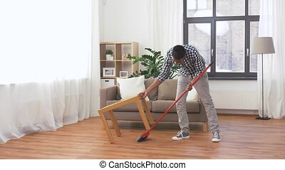 man with broom cleaning floor at home
