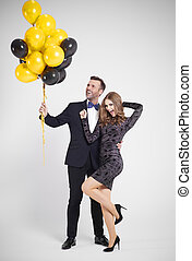 Man with bunch of balloons embracing woman