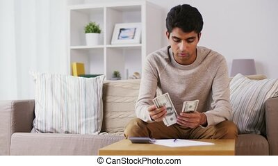 man with calculator counting money at home - savings,...