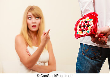 Man with candy bunch flowers and unhappy woman. - Man with...