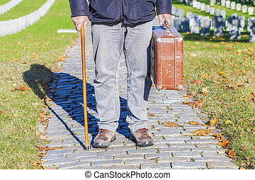 Man with cane and old suitcase in cemetery