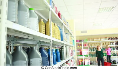 man with canister of motor oil in auto store. retail motor...