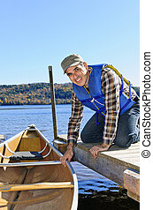 Man with canoe - Man holding canoe at dock on Lake of Two...