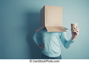 A man with a cardboard box on his head is holding a paper cup