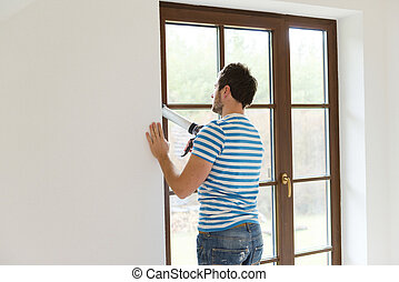 Man with caulking gun - Man applying silicone sealant with ...