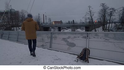 Man with cell taking video of moving train in winter city