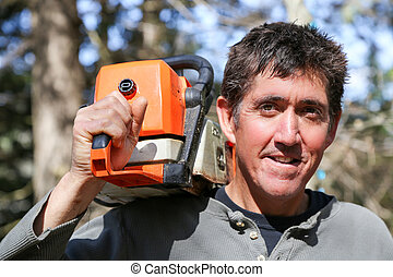 Man with chainsaw - A man with a chainsaw slung over his...