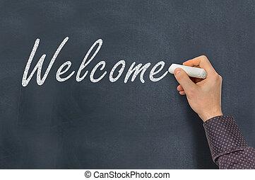 Man with chalk writing Welcome on blackboard