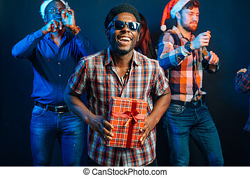 man with charming smile holding Christmas gift in hands