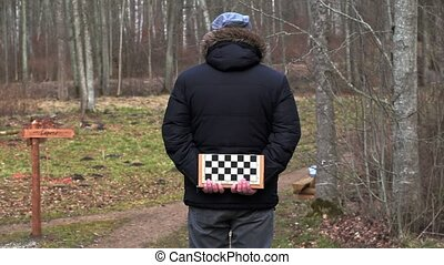 Man with chess board talking with friend - Man with chess...