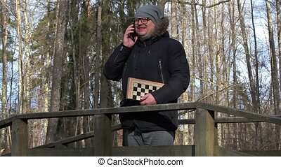 Man with chess talking on smart phone in park on bridge