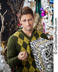 Man With Christmas Gift Biting Lips In Store