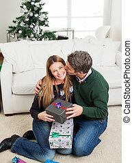 Man With Christmas Gift Kissing Woman On Cheek