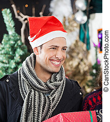 Man With Christmas Present Smiling In Store