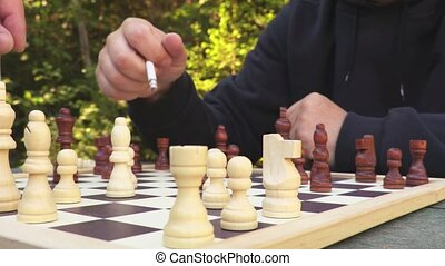 Man with cigarette playing chess at outdoor