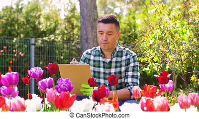 man with clipboard and flowers at summer garden - gardening ...