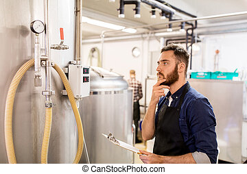 man with clipboard at craft brewery or beer plant -...