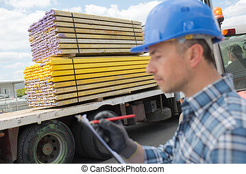 Man with clipboard beside delivery of wood