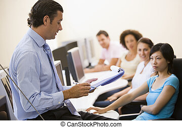 Man with clipboard giving lecture in computer class