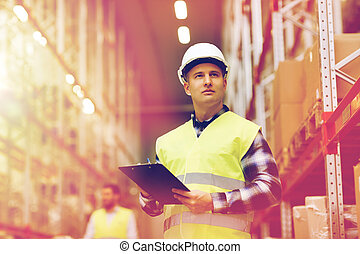 man with clipboard in safety vest at warehouse - wholesale,...