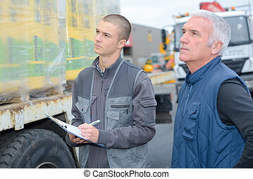 Man with clipboard looking at delivery on lorry