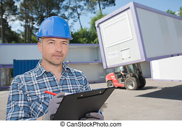 Man with clipboard wearing hardhat