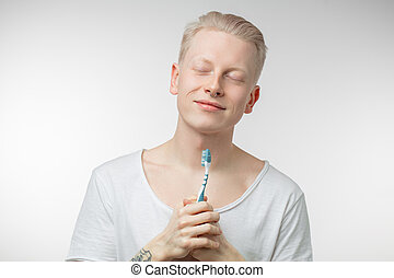 Man with closed eyes holding toothbrush in hand. Dental care...