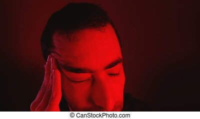 Man with closed eyes rubs his head and suffering from pain....