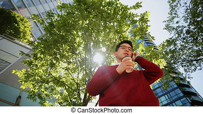 Man with coffee cup talking on mobile phone on street 4k -...