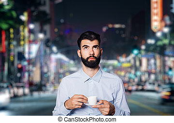 Man with coffee in city