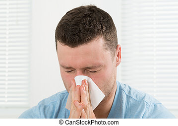 Man With Cold Blowing His Nose At Home